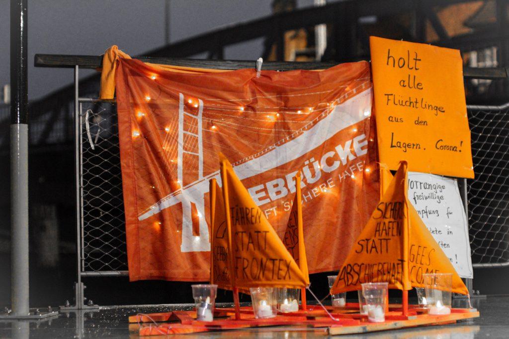 """Zu sehen ist ein orangenes selbstgebasteltes Bötchen mit beschrifteten Segeln vor einem orangenen & mit Lichterketten dekorierten Seebrücken-Transpi sowie mehreren Plakaten mit u.a. der Aufschrift """"holt alle Flüchtlinge aus den Lagern!""""."""
